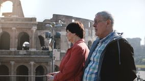 Happy active senior Caucasian tourist couple enjoying the view of famous Coliseum together during trip to Rome, Italy. stock video footage