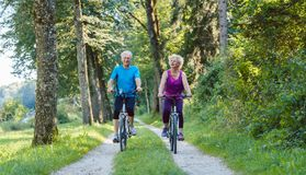 Happy and active senior couple riding bicycles outdoors in the p stock photography