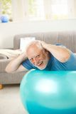 Happy active senior exercises on fit ball. At home, looking at camera, laughing Royalty Free Stock Image