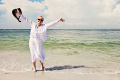 Happy active senior woman. A smiling elderly woman on the beach with arms up royalty free stock images