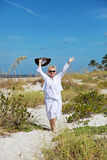 Happy active senior woman. A smiling senior woman walking on the beach with arms up royalty free stock photos