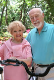 Happy Active Seniors. A happy, active senior couple going for a bike ride royalty free stock photography