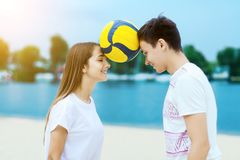 Happy romantic couple playing with soccer ball in summer stock image