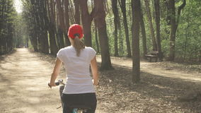 Happy active sportive young woman in red cap cycling through sunny park on summer`s day. Happy active sportive young woman in red cap and white t-shirt riding stock video