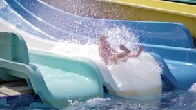 Happy active tanned boy ride on water slide at aquapark having positive emotion slow motion