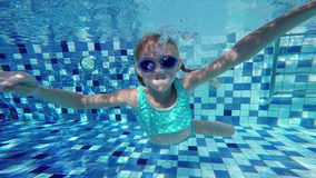 Happy active underwater child swimming in pool at the day time. stock video footage