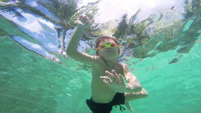 Happy active underwater child swimming in pool stock footage