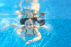 Happy active underwater child swims in pool Stock Image