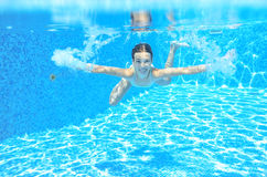 Happy active underwater child swims in pool, beautiful healthy girl swimming Stock Photo