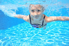 Happy active underwater child swims in pool, beautiful healthy girl swimming stock photos
