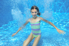 Happy active underwater child swims in pool Royalty Free Stock Images