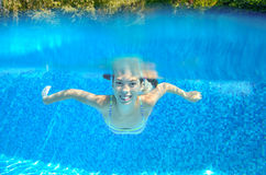 Happy active underwater child swims in pool Stock Images