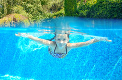 Happy active underwater child swims in pool Royalty Free Stock Photos
