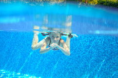 Happy active underwater child swims in pool Royalty Free Stock Photography