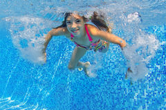 Happy active underwater child swims and dives in pool Royalty Free Stock Image