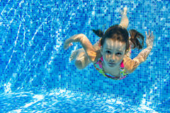 Happy active underwater child swims and dives in pool Royalty Free Stock Photos