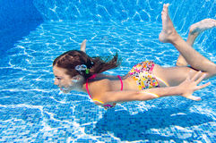 Happy active underwater child swims and dives in pool Royalty Free Stock Images