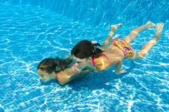 Happy active underwater children swim in pool. Beautiful healthy girls swimming and having fun on family summer vacation, kids sport concept Royalty Free Stock Images
