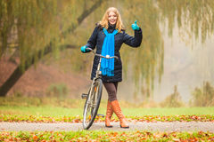 Happy active woman with bike in autumn park. Royalty Free Stock Photo