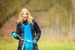 Happy active woman with bike in autumn park. Happy active woman with bike bicycle in fall autumn park. Glad young girl in jacket and scarf relaxing. Healthy Stock Photo