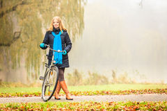Happy active woman with bike in autumn park. Stock Photography
