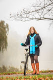 Happy active woman with bike in autumn park. Royalty Free Stock Images