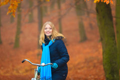 Happy active woman riding bike in autumn park. Happy active woman riding bike bicycle in fall autumn park. Glad young girl in jacket and scarf relaxing. Healthy Stock Images