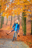 Happy active woman riding bike in autumn park. Happy active woman riding bike bicycle in fall autumn park. Glad young girl in jacket and scarf relaxing. Healthy Royalty Free Stock Photography