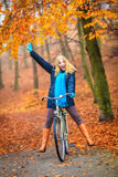 Happy active woman riding bike in autumn park. Happy active woman riding bike bicycle in fall autumn park. Glad young girl in jacket and scarf relaxing. Healthy Royalty Free Stock Photos