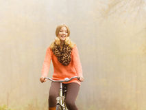 Happy active woman riding bike in autumn park. Happy active woman riding bike bicycle in fall autumn park. Glad young girl relaxing. Healthy lifestyle Stock Images