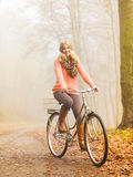 Happy active woman riding bike in autumn park. Royalty Free Stock Photo