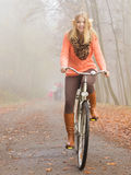 Happy active woman riding bike in autumn park. Stock Photos