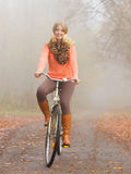 Happy active woman riding bike in autumn park. Royalty Free Stock Photos