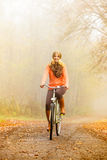 Happy active woman riding bike in autumn park. Royalty Free Stock Images