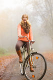 Happy active woman riding bike in autumn park. Royalty Free Stock Photography