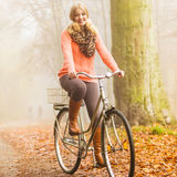 Happy active woman riding bike in autumn park. Stock Photography