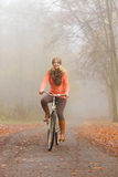 Happy active woman riding bike in autumn park. Stock Photo