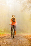 Happy active woman riding bike in autumn park. Royalty Free Stock Image