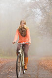 Happy active woman riding bike in autumn park. Stock Image