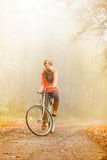 Happy active woman riding bike in autumn park. Happy active woman riding bike bicycle in foggy fall autumn park. Glad young girl in sweater and earmuffs Royalty Free Stock Images