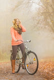 Happy active woman riding bike in autumn park. Happy active woman riding bike bicycle in foggy fall autumn park. Glad young girl in sweater and earmuffs Stock Image