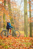 Happy active woman riding bike in autumn park. Happy active woman girl riding bike bicycle relaxing in fall autumn park. Healthy lifestyle Royalty Free Stock Images
