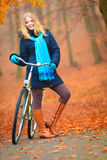 Happy active woman riding bike in autumn park. Happy active woman girl riding bike bicycle relaxing in fall autumn park. Healthy lifestyle Stock Images