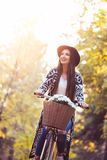 Happy active woman riding bike bicycle in fall autumn park. Happy active woman riding bike bicycle in  autumn park Royalty Free Stock Image