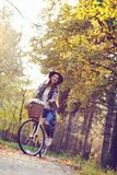 Happy active woman riding bike bicycle in fall autumn park Stock Photos