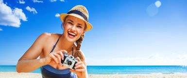 Happy active woman on seacoast taking photo with digital camera Stock Image