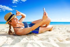Happy active woman on seacoast taking selfie with mobile phone Royalty Free Stock Photo