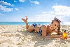 Happy active woman in swimsuit on seashore with sun cream. Sun kissed beauty. happy active woman in swimsuit on the seashore with sun cream Stock Image