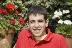 Happy adolescent with braces. Happy teenager with braces on teeth in the garden Stock Photo