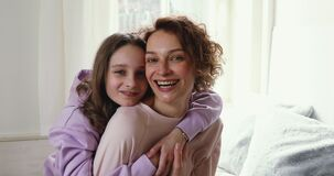Happy adolescent child girl cuddling back of smiling mother.